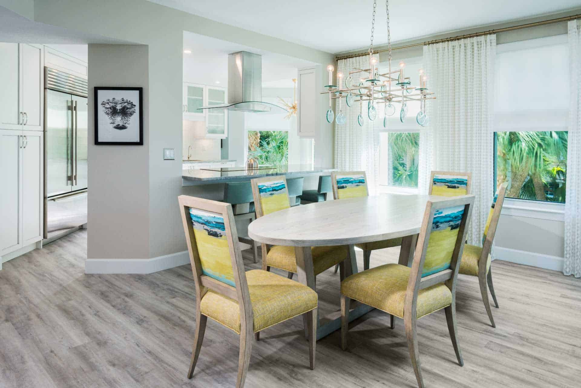 Six-seat dining room with chandelier and open counter to kitchen area